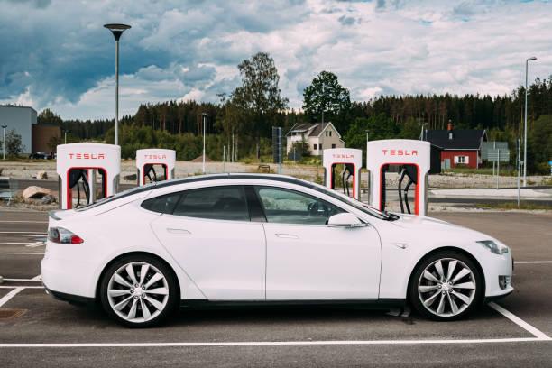 vit färg tesla model s p85 bil parkerad på laddstationen. tesla model s är en full-sized alla elektriska fem-dörrars, lyx liftback, producerad av tesla inc - elbilar laddning sverige bildbanksfoton och bilder