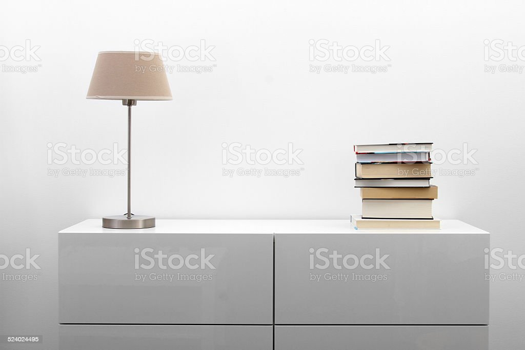 white commode with lamp and books in bright minimalism interior stock photo