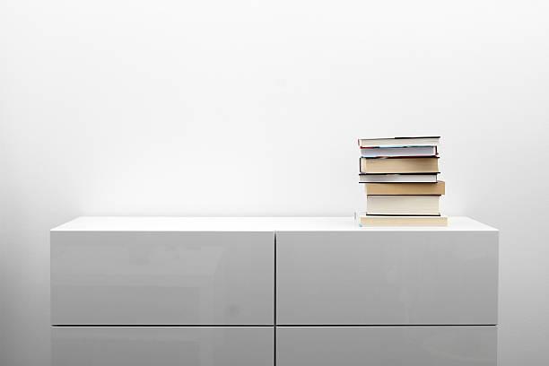 white kommode mit stapel bücher auf minimalismus innenraum - schubladenkommode weiß stock-fotos und bilder