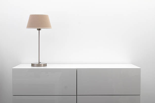 white commode with table lamp in bright minimalism interior stock photo