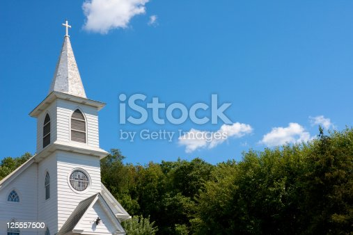 Traditional White American community church shot against a blue sky and trees.