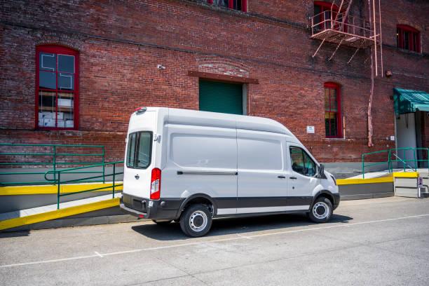 weißer kompakter, beliebter fracht-minivan für lokale lieferungen und business-standing auf dem lagerparkplatz - van stock-fotos und bilder