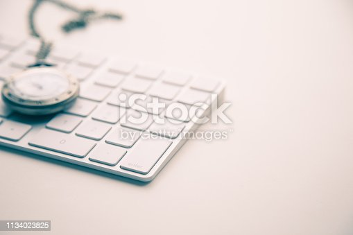 istock A white computer keyboard and a watch necklace on white floor. 1134023825