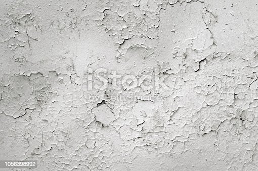 istock White concrete wall of the old house with curly cracks and swollen white paint. Background 1056398992