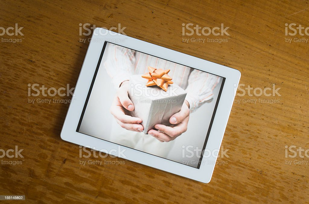 White contemporary digital tablet with gift photo on wood table royalty-free stock photo