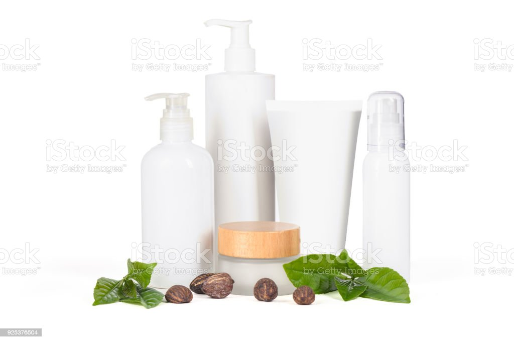 White cosmetic bottles and containers and shea butter nuts - foto stock