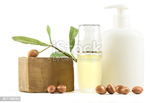 istock White cosmetic bottles and containers with argan fruits 921796250