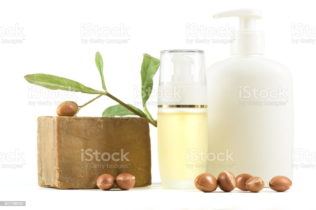White cosmetic bottles and containers with argan fruits - foto stock