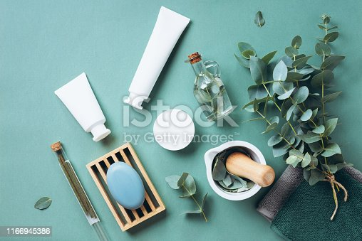 istock White cosmetic bottles, eucalyptus flowers, towels, soap on green background. Top view, flat lay. Natural organic beauty product concept. Spa, skin care, body treatment 1166945386
