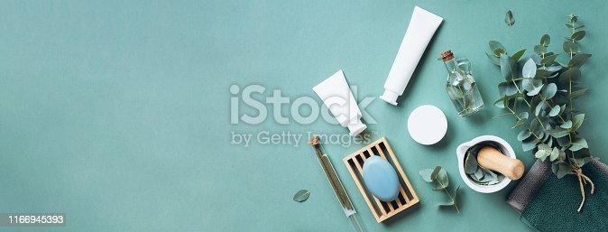 istock White cosmetic bottles, eucalyptus flowers, towels, soap on green background. Top view, flat lay. Natural organic beauty product concept. Spa, skin care, body treatment 1166945393