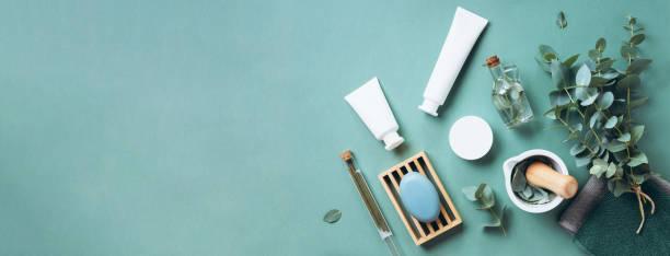 witte cosmetische flessen, eucalyptus bloemen, handdoeken, zeep op groene achtergrond. top uitzicht, vlakke lag. natuurlijke biologische schoonheid productconcept. spa, huidverzorging, lichaamsbehandeling - creme huid stockfoto's en -beelden