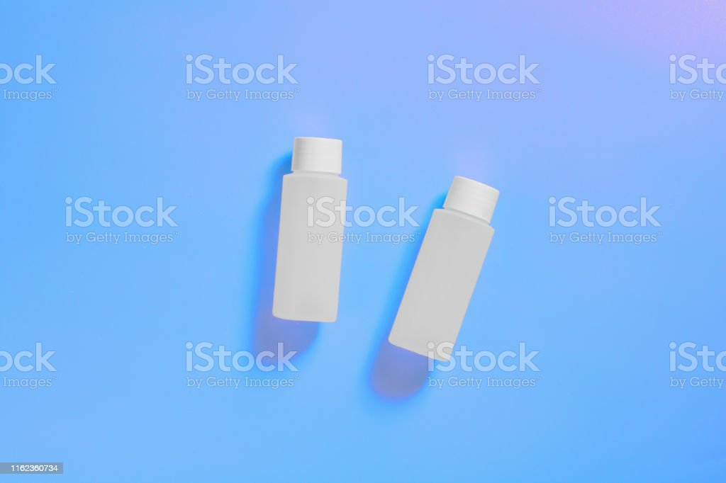 White cosmetic bottles on a blue neon background, bottle for cosmetic...
