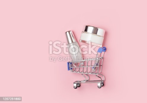 White cosmetic jars with cream lie in a shopping trolley on a pink background. Online home shopping.