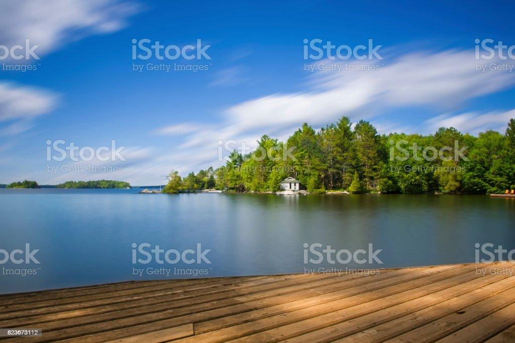White cottage facing calm lake stock photo