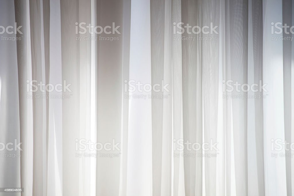 A white cotton curtain draping stock photo