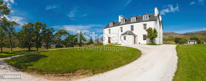 Large family home set in idyllic rural landscape below blue summer skies. ProPhoto RGB profile for maximum color fidelity and gamut.