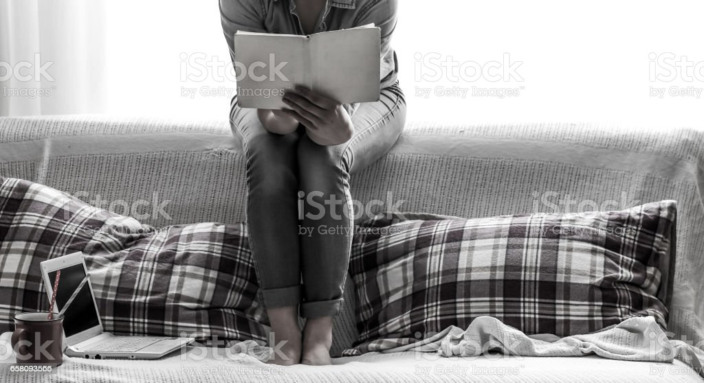 White cozy bed and a beautiful girl, reading a book, concepts of home and comfort royalty-free stock photo