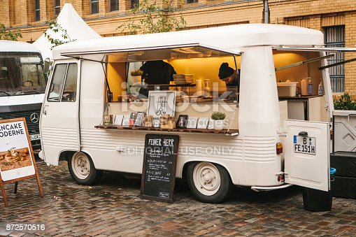 Berlin, October 1, 2017: White cozy small mini bus food market with snacks and coffee and two sellers