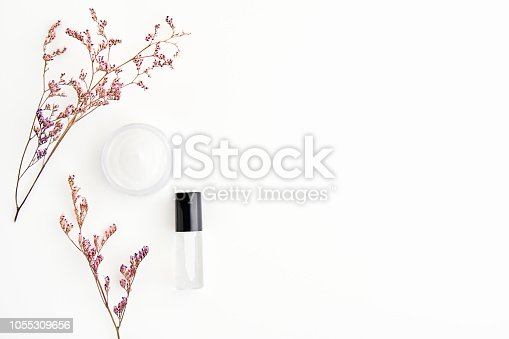 927626522 istock photo White cream bottle placed and flowers, Blank label package for mock up on a white background. The concept of natural beauty products. 1055309656