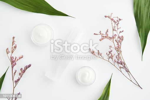 927626522 istock photo White cream bottle placed, Blank label package for mock up on a green foliage background and flowers. The concept of natural beauty products. 1011306426