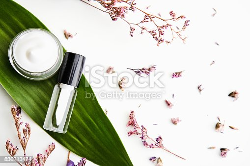 927626522 istock photo White cream bottle placed, Blank label package for mock up on a green foliage background and flowers. The concept of natural beauty products. 836213474