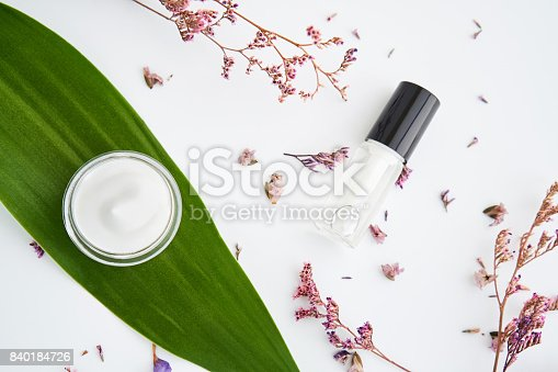 927626522 istock photo White cream bottle placed, Blank label package for mock up on a green foliage background and flowers. The concept of natural beauty products. 840184726