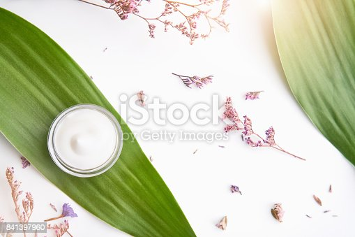 istock White cream bottle placed, Blank label package for mock up on a green foliage background and flowers. The concept of natural beauty products. 841397960