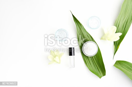 istock White cream bottle placed, Blank label package for mock up on a green foliage background and flowers. The concept of natural beauty products. 927626522