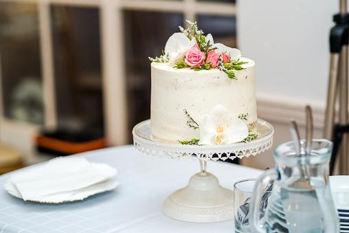 White cream wedding cake with flower decoration on it.