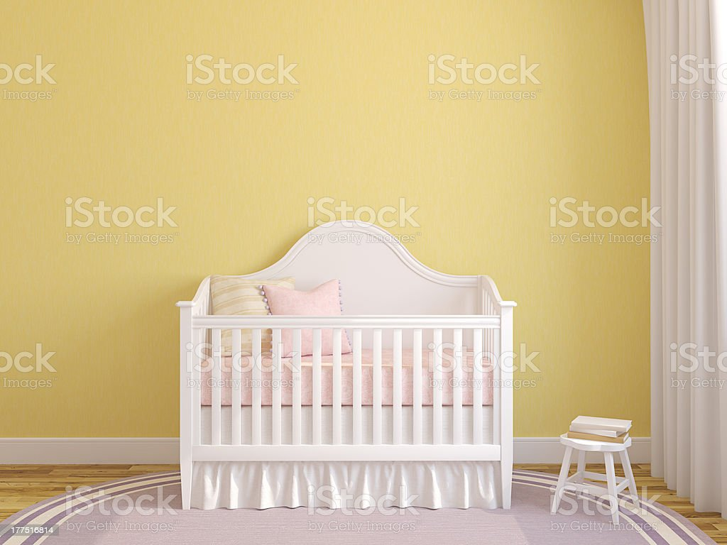 White crib in the interior of a yellow baby nursery royalty-free stock photo