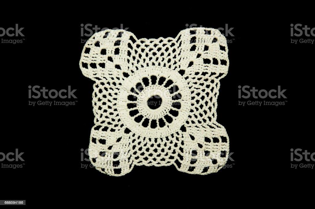 White crocheted coaster on black background. Not isolated. Lace doily. stock photo