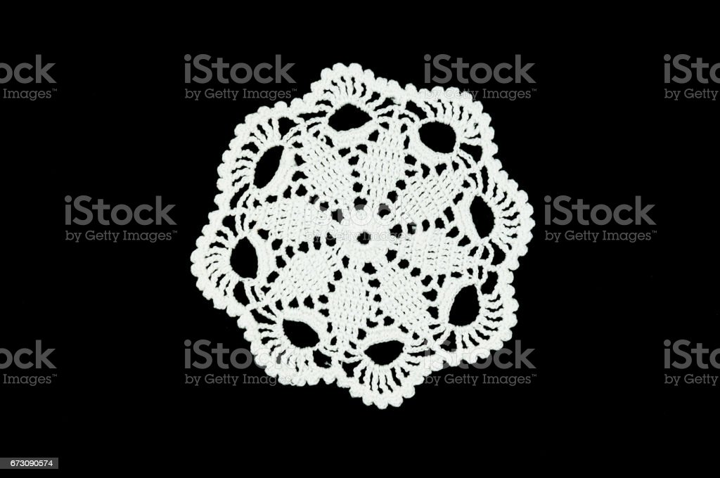 White crocheted coasters on black background. Not isolated. Lace doily. stock photo