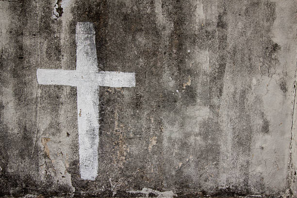 White cross on cemetery wall stock photo