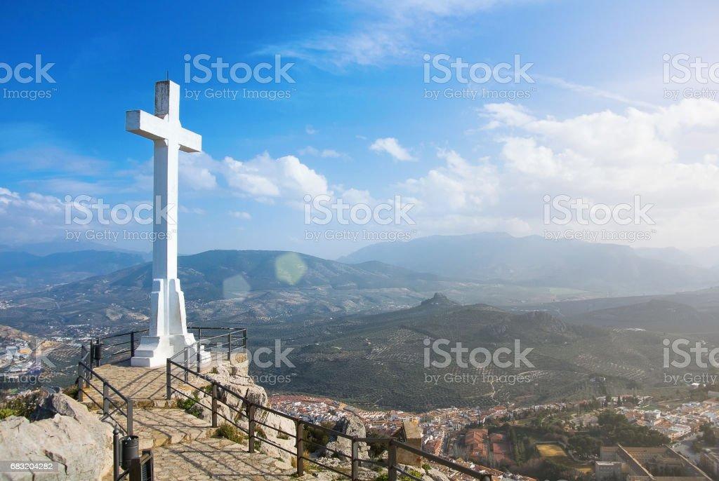 ハエン山、晴れた日に、スペイン、アンダルシア地方の背景に山脈 Magina 山と町のシンボルの上の白い十字。 ロイヤリティフリーストックフォト