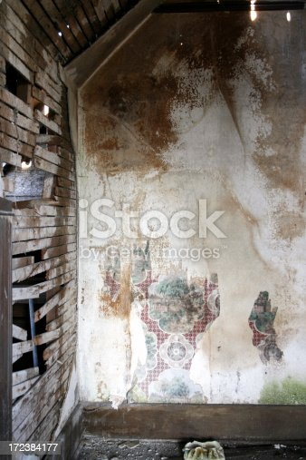 168248826 istock photo White crumbling water damaged plaster walls with wallpaper 172384177