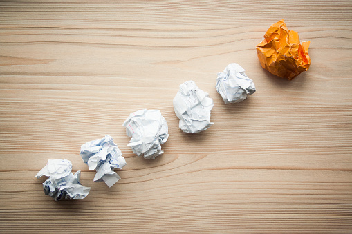 istock White crumpled paper balls folded in line with orange different paper ball on the top. Concept of problem solution, think different, think out of the box, leadership. 1146260816