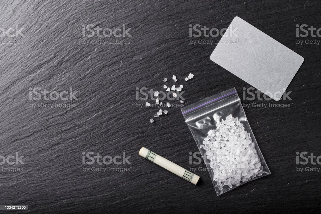 white crystals of drugs in a bag on a black table. stock photo