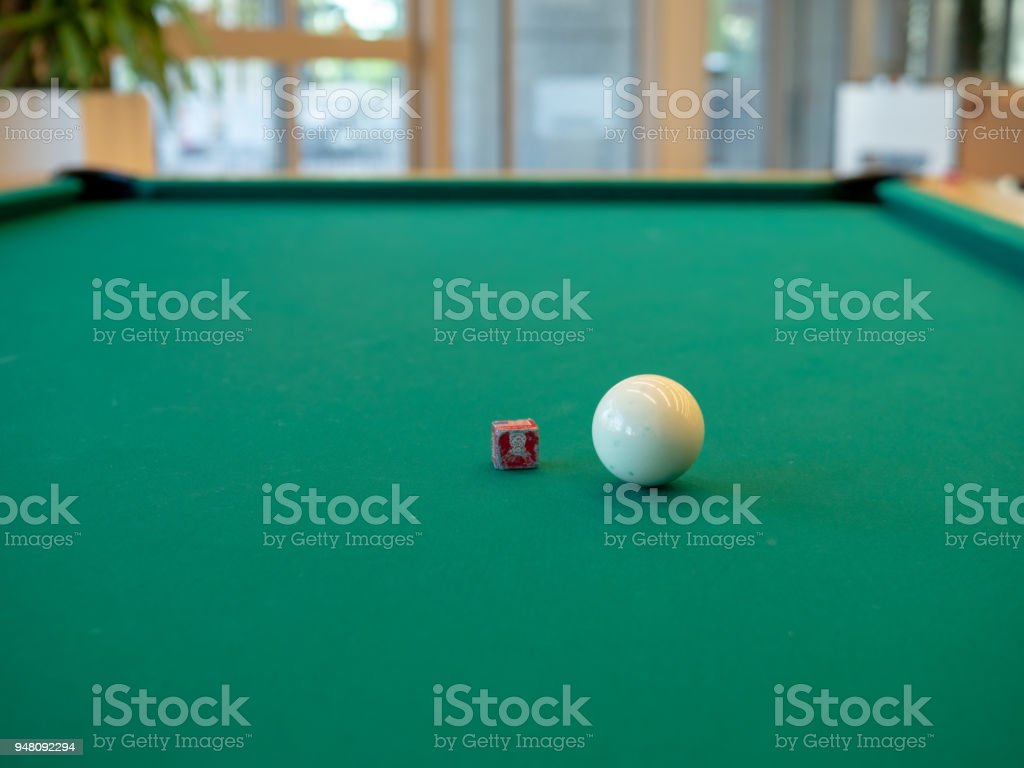 White cue ball and chalk sitting on billiards table ready for pool