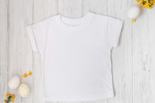 White Cuffed T-Shirt mockup with Easter eggs and flowers, flat lay