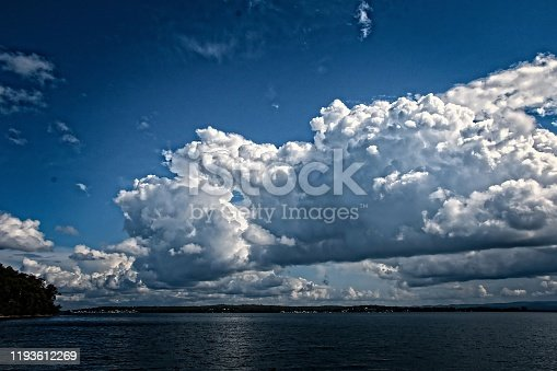 White Cumulus cloud in blue sky at sea with water reflections. East Coast, Australia