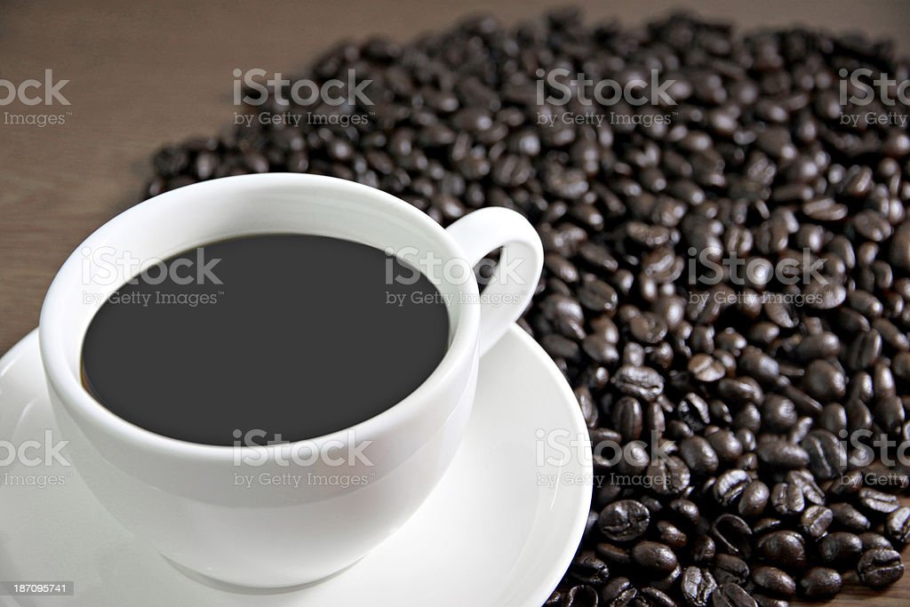 White cup and coffee beans on the table old wood. royalty-free stock photo
