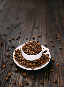 White cup and dish with coffee beans. Isometric view rustic concept.