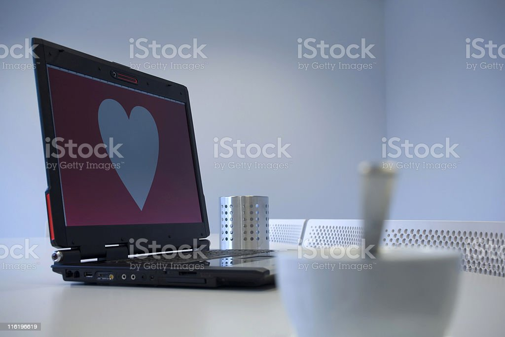 white cup and heart shape on a computer monitor stock photo