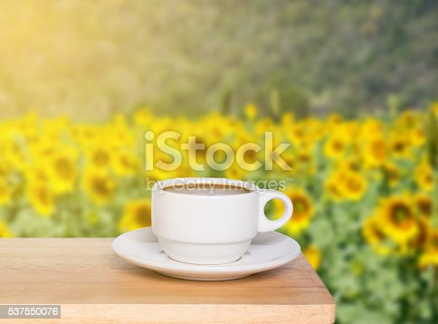 istock white cup coffee on wood desk and sunflowers background 537550076