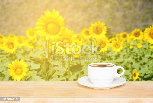 istock white cup coffee on wood desk and sunflowers background 537600482