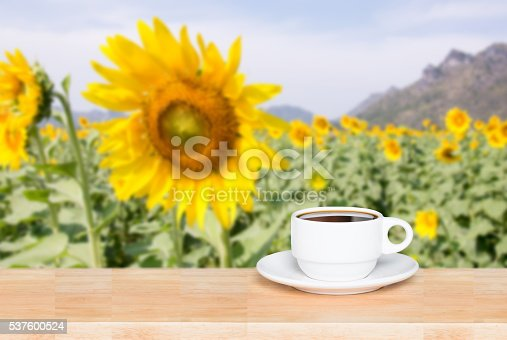 istock white cup coffee on wood desk and sunflowers background 537600524
