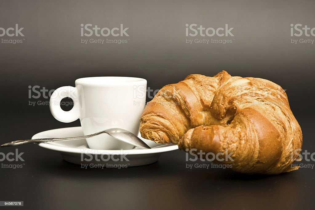white cup coffee, spoon and croissant on black background royalty-free stock photo