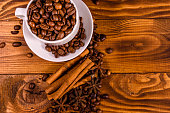 White cup filled with coffee beans, star anise and cinnamon sticks on rustic wooden table. Top view