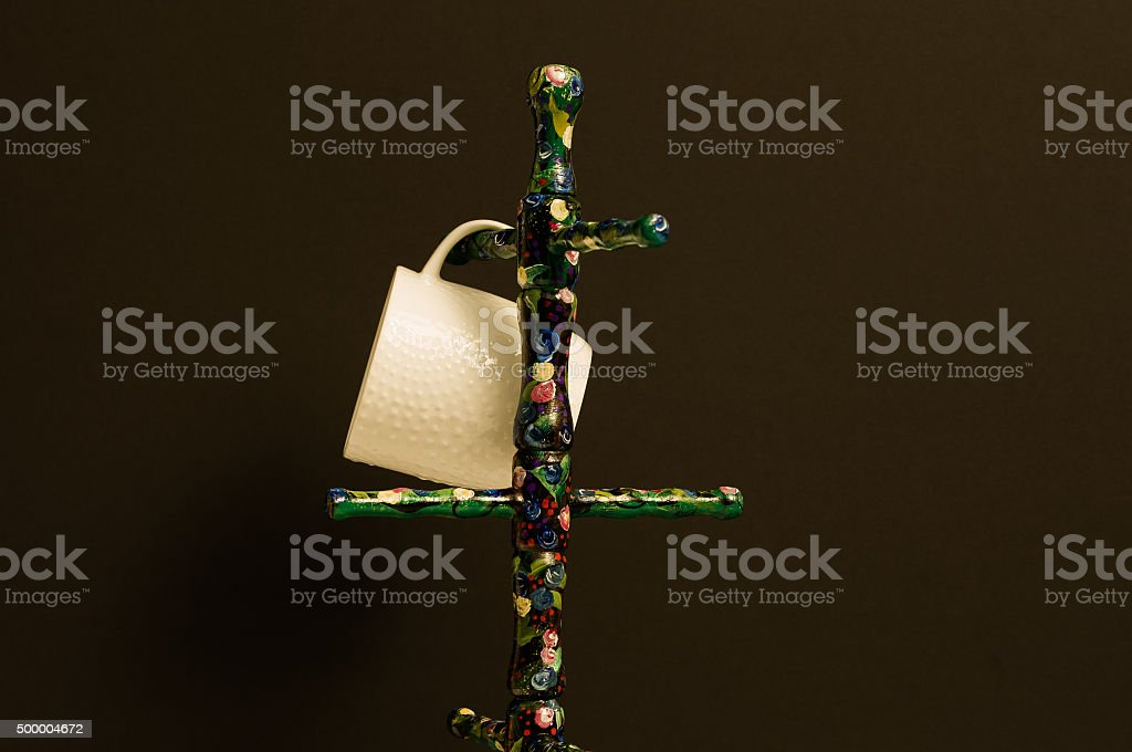 White cup hanging on  painted folk art stand stock photo