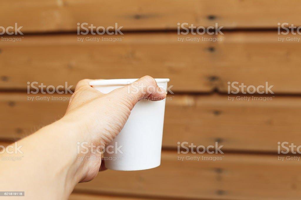 white cup in the hand royaltyfri bildbanksbilder